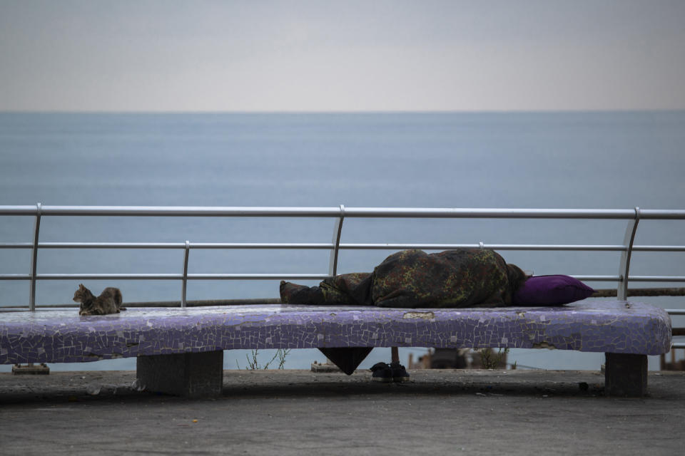 A cat sits next to a homeless woman sleeping on the Mediterranean Sea corniche in Beirut, Lebanon, Sunday, July 19, 2020. Lebanon should quickly form a reform-minded government to carry out badly needed reforms to help get the tiny country out of its severe economic crisis where the Real GDP growth is projected to contract nearly 20% in 2020 and a crash in local currency led to triple-digit inflation rates, the World Bank said Tuesday. (AP Photo/Hassan Ammar)