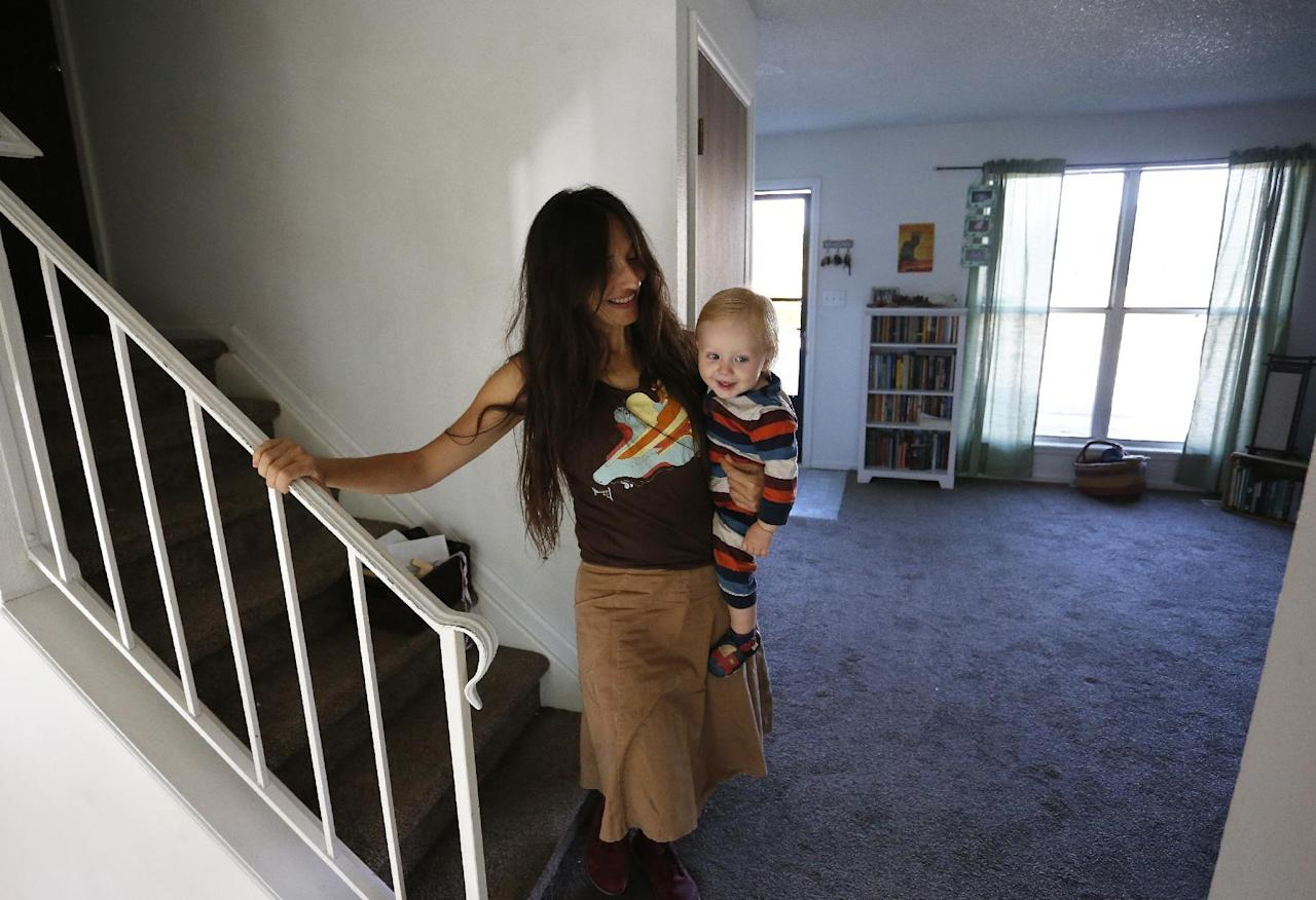 In this Thursday, Oct. 20, 2016 photo, vegan mother Fulvia Serra carries her 1-year-old baby, Sebastiano, at home in Fort Collins, Colo. Serra, originally from Italy, and her husband, Scott, are raising their son vegan. Despite criticism and innuendo from some circles, pediatricians and nutritionists agree it's perfectly healthy to feed babies a vegan diet. However, parents need to be well-informed about the nutritional elements different foods offer, and work closely with their doctor or health care provider. (AP Photo/Brennan Linsley)