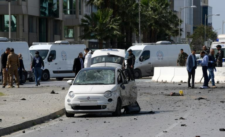 Police and forensic experts gather at the scene of an explosion near the US embassy in Tunis