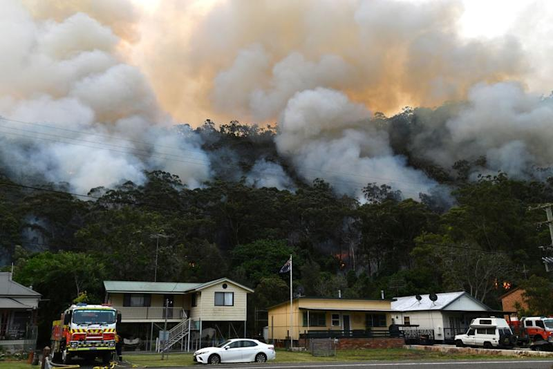 Smoke and flames from a back burn, conducted to secure residential areas from encroaching bushfires, are seen close to homes at the Spencer area in Central Coast on December 9. Source: Getty