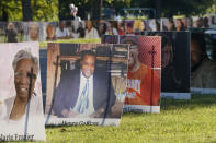 Some of the nearly 900 large poster-sized photos of Detroit victims of COVID-19 are displayed, Monday, Aug. 31, 2020 on Belle Isle in Detroit. Families have a chance to take one last public look at their lost loved ones in the nation's first citywide memorial to honor victims of the pandemic. Mourners will join 14 consecutive funeral processions to drive past the photos of their loved ones staked around the island. (AP Photo/Carlos Osorio)