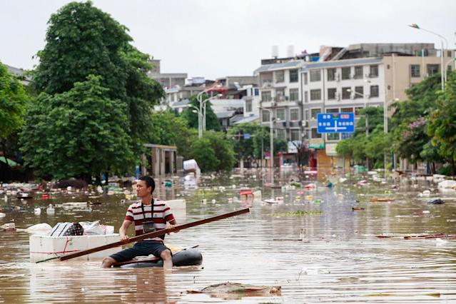 <p>A man uses an improvised flotation device to move through floodwaters on a flooded street in Liuzhou, Guangxi province, China, July 3, 2017. (Photo: STR/AFP/Getty Images) </p>