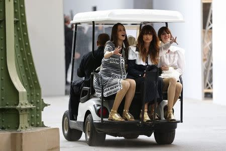 Models sit in a car to return backstage during the German designer Karl Lagerfeld Spring/Summer 2015 women's ready-to-wear collection show for fashion house Chanel during Paris Fashion Week September 30, 2014. REUTERS/Charles Platiau