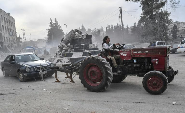 A fighter tows a looted vehicle after Turkish-led forces seized control of the northwestern Syrian city of Afrin from the Kurdish People's Protection Units (YPG) on March 18, 2018