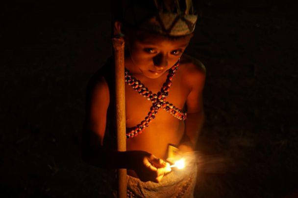 PHOTO: A young member of Peru's Wachiperi indigenous group lights a match during a ceremony in the Amazon village of Santa Rosa de Huacaria. (Neil Giardino/ABC News)