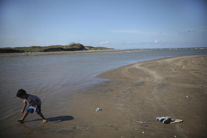 In this Aug. 2, 2019 photo, a child collects seashells as he walks along the shoreline in Playa Bagdad close to the mouth of the Rio Grande where between the U.S. and Mexico lies an expanse of water, perhaps 25 yards (meters) wide, so shallow that you can walk across at low tide, but few people do. (AP Photo/Emilio Espejel)