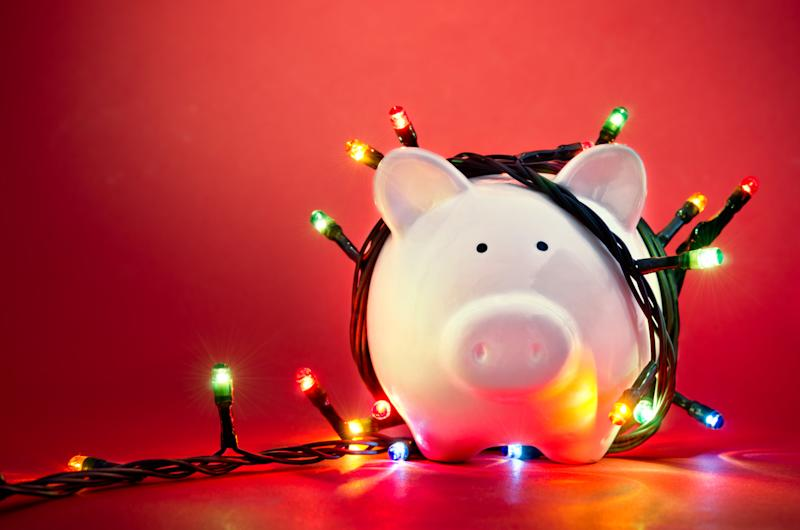 Piggy bank wrapped in Christmas string lights. Photo: Getty