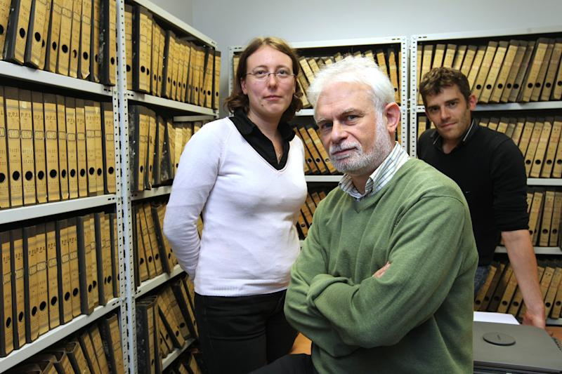 Historian Emmanuel Gerard, center, and researchers Widukind De Ridder, right, and Françoise Muller, pose at an archive room in Brussels, Monday, Oct. 2, 2012. Now, 62 years after Belgian politician Julien Lahaut was murdered, even as the European financial crisis is squeezing budgets dry, the Belgian government has approved fresh funds to solve the crime. (AP Photo/Yves Logghe)