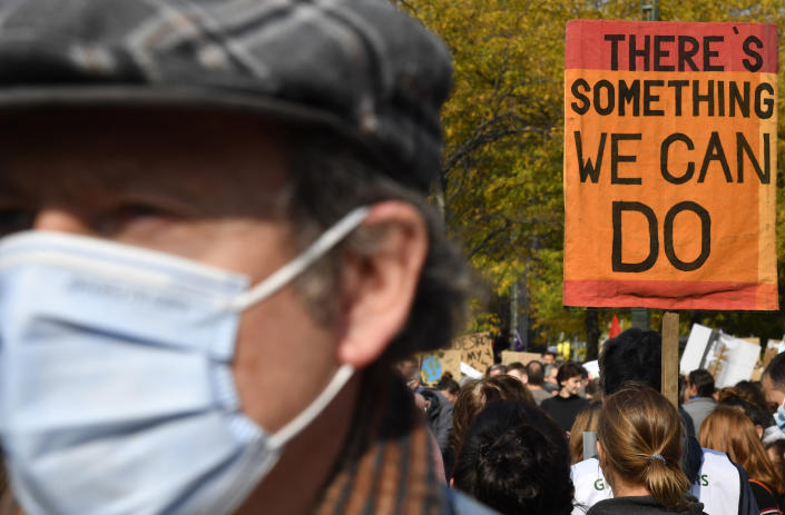 A woman carries a sign as she participates in a climate march in Brussels, Sunday, Oct. 10, 2021. Some 80 organizations are joining in a climate march through Brussels to demand change and push politicians to effective action in Glasgow later this month.(AP Photo/Geert Vanden Wijngaert)