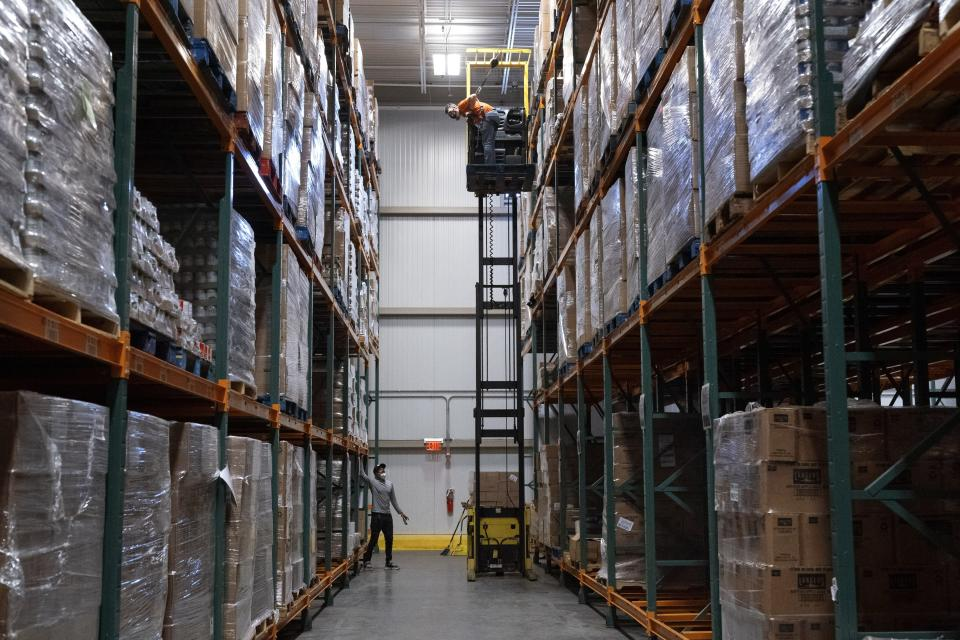 Workers shout to each other from five levels of stored food items at the warehouse of The Capital Area Food Bank, Tuesday, Oct. 5, 2021, in Washington. (AP Photo/Jacquelyn Martin)