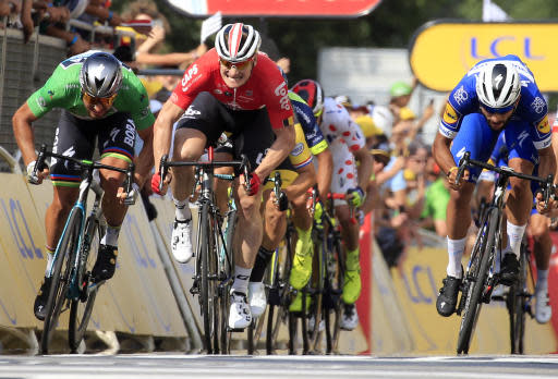 Colombia's Fernando Gaviria,right, crosses the finish line to win the fourth stage of the Tour de France cycling race over 195 kilometers (121 miles) with start in La Baule and finish in Sarzeau, France, Tuesday, July 10, 2018. Slovakia's Peter Sagan, left, finished second and Germany's Andre Greipel, center, third. (AP Photo/Peter Dejong)