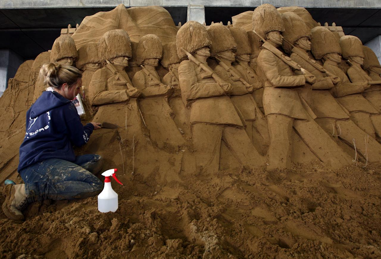 Nicola Wood of the U.K. finishes a sand sculpture titled 'Imperial Guards In Front of The Palace' at Sand Museum located in the Tottori Dune on April 1, 2012 in Tottori, Japan. (Photo by Buddhika Weerasinghe/Getty Images)