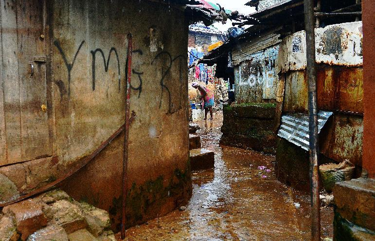 A woman stands in Kroo town slum in Freetown on August 13, 2014
