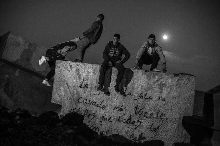 Moroccan kids sit on the breakwater next to Melilla´s harbor in 2014. (Photo: José Colón/MeMo for Yahoo News)