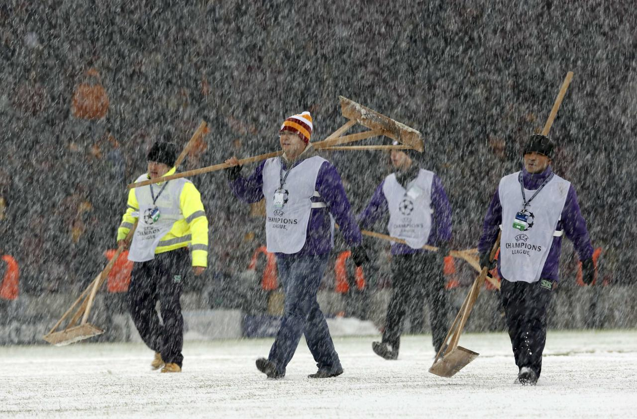 Workers rush to clean the snow from the pitch after the Champions League soccer match between Galatasaray and Juventus was paused for 20 minutes due heavy snowfall in Istanbul December 10, 2013. REUTERS/Murad Sezer (TURKEY - Tags: SPORT SOCCER)