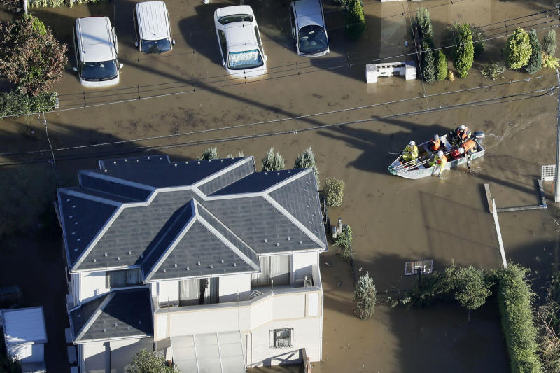 Rescuers on a boat make their way through flooded residential area hit by Typhoon Hagibis, in Sakado, on the outskirts of Tokyo, Sunday, Oct. 13, 2019. Rescue efforts for people stranded in flooded areas are in full force after a powerful typhoon dashed heavy rainfall and winds through a widespread area of Japan, including Tokyo.(Kyodo News via AP)