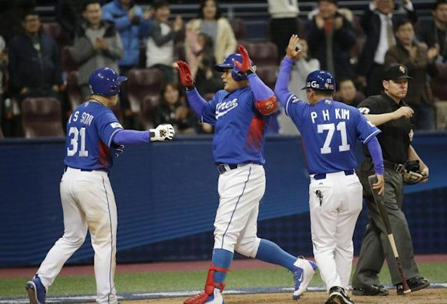 South Korea's Kim Tae-kyun, center, is greeted by Son Ah-seop and Kim Pyung-ho, right, after hitting a two run homer against Taiwan's pitcher Chun Hung Wen during the 10th inning of their first round game of the World Baseball Classic at Gocheok Sky Dome in Seoul, South Korea, Thursday, March 9, 2017. (AP Photo)