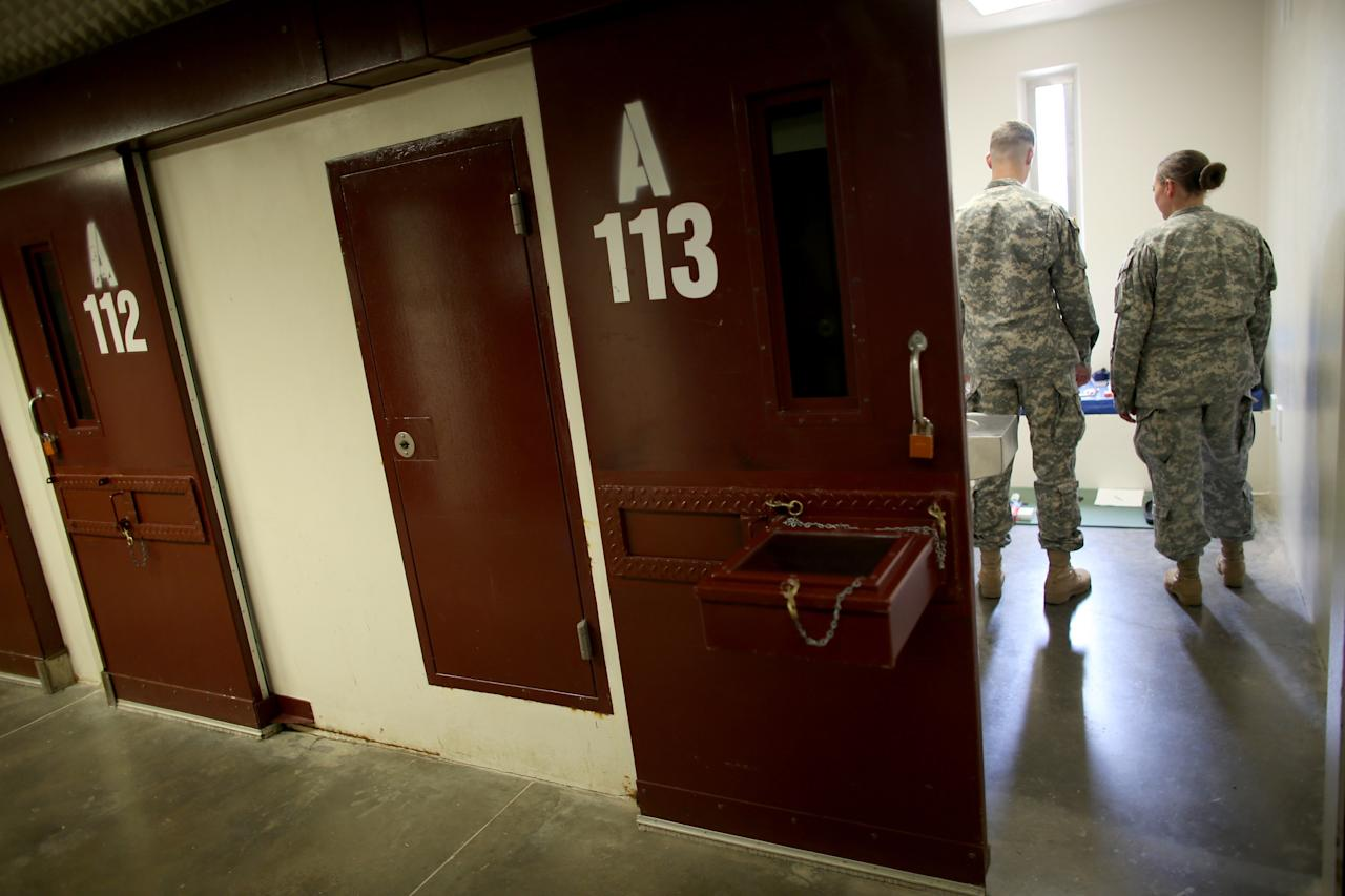 GUANTANAMO BAY, CUBA - JUNE 25: (EDITORS NOTE: Image has been reviewed by the U.S. Military prior to transmission.) U.S. Army personnel look at items in a static display setup for visitors in a prison cell in camp V where prisoners are housed in the single cell facility at the U.S. military prison for 'enemy combatants' on June 25, 2013 in Guantanamo Bay, Cuba. President Barack Obama has recently spoken again about closing the prison which has been used to hold prisoners from the invasion of Afghanistan and the war on terror since early 2002. (Photo by Joe Raedle/Getty Images)