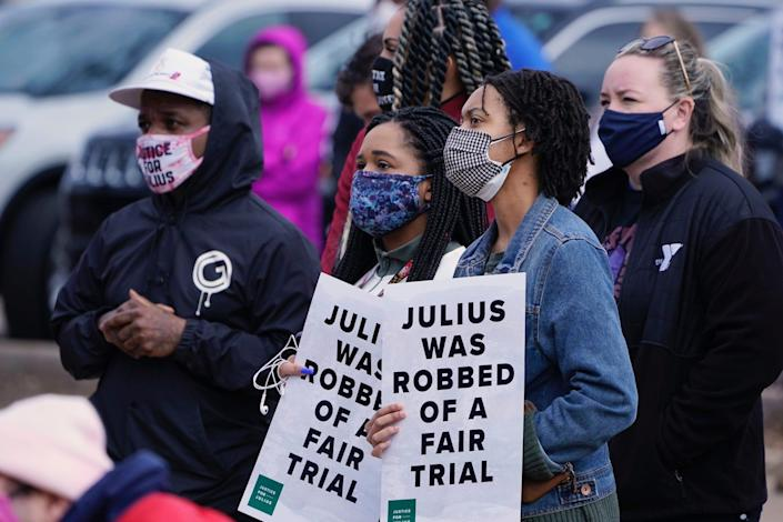 Trinity Carpenter, center left, and Elise Miller, center right, hold signs at a rally for Julius Jones, Thursday, Feb. 25, 2021, in Oklahoma City.