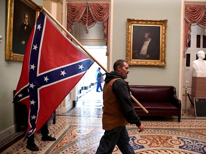 <p>A supporter of President Donald Trump carries a Confederate battle flag on the second floor of the US Capitol.</p> ((Reuters))