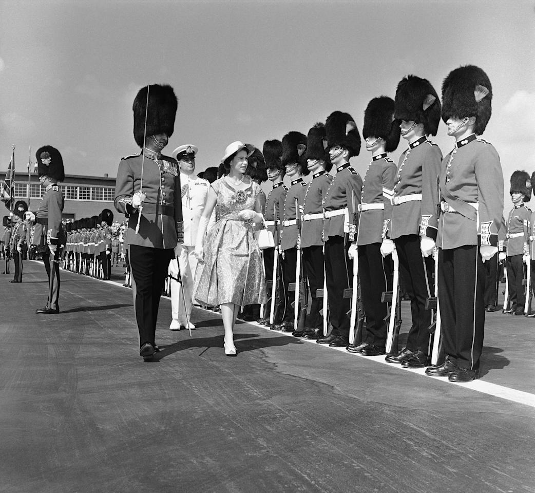"FILE In this June 29, 1959 photo, a member of the Royal Regiment of Canada towers over Queen Elizabeth II during review of guard of honor in Toronto. Decades have passed since Canadians replaced ""God Save the Queen"" with ""O Canada,"" but royalty-lovers are in for a thrill Thursday, June 30, 2011, when Prince William and his bride come visiting. Those who leaf through the country's updated citizenship guide will find the oath of allegiance to Queen Elizabeth II is now at the front. The pamphlet is a reflection of something deeper , Prime Minister Stephen Harper's ambition to foster a conservative national identity in which the royal connection plays a key role. (AP Photo)"