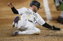 Colorado Rockies' Trevor Story scores on a double by Charlie Blackmon off Arizona Diamondbacks relief pitcher Kevin Ginkel during the eighth inning of a baseball game Tuesday, Aug. 11, 2020, in Denver. The Rockies won 8-7. (AP Photo/David Zalubowski)
