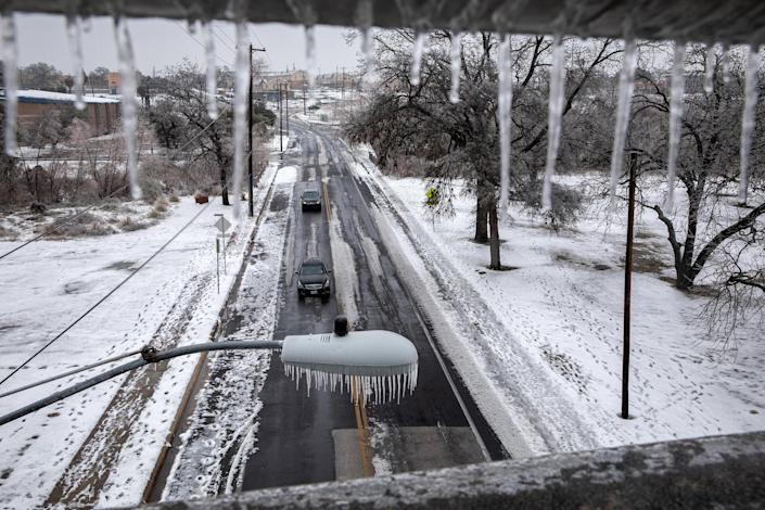 Ice and snow cover an area as seen through an overpass railing in Austin, Texas., on Feb. 17