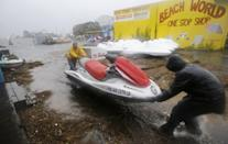 Ron Croker, left, and Tim Wood, move a jet ski on wheels to a safer location as water floods the dock, as Hurricane Sandy bears down on the East Coast, Monday, Oct. 29, 2012, in Ocean City, Md. (AP Photo/Alex Brandon)