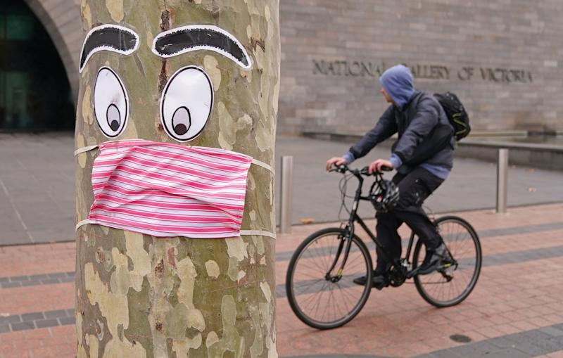 A man rides past a tree with a face mask and eyes stapled to it in Melbourne, Sunday, June 21, 2020.