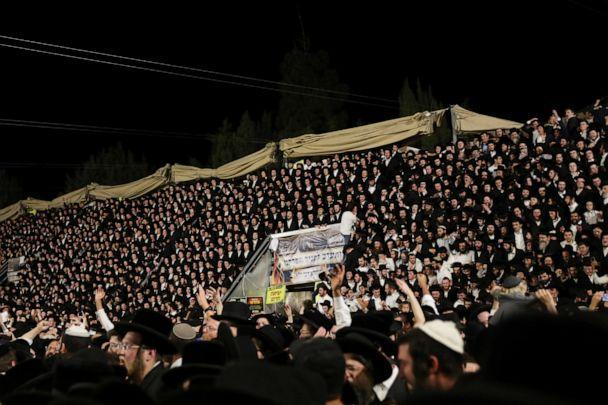 PHOTO: Jewish worshippers sing and dance as they stand on tribunes at the Lag B'Omer event in Mount Meron, northern Israel, April 29, 2021.  (Stringer/Reuters)