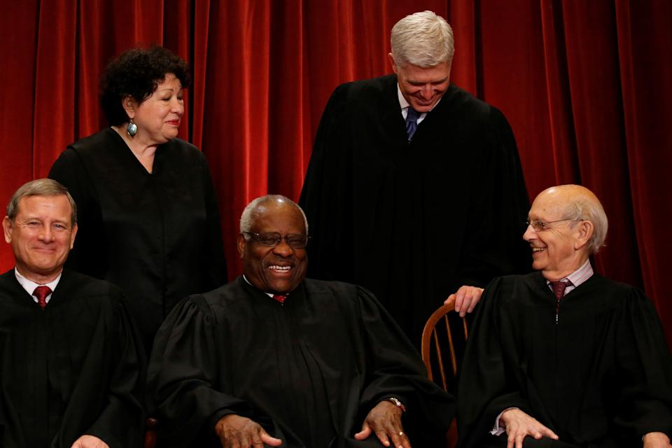 U.S. Justice Neil Gorsuch (top R) leans in to speak to Justice Stephen Breyer (bottom R) as the members of the U.S. Supreme Court including Chief Justice John Roberts (seated L), Justice Clarence Thomas (seated C) and Justice Sonia Sotomayor (top L) gather for a new family photo with Gorsuch, their most recent addition, at the Supreme Court building in Washington, D.C., U.S., June 1, 2017.