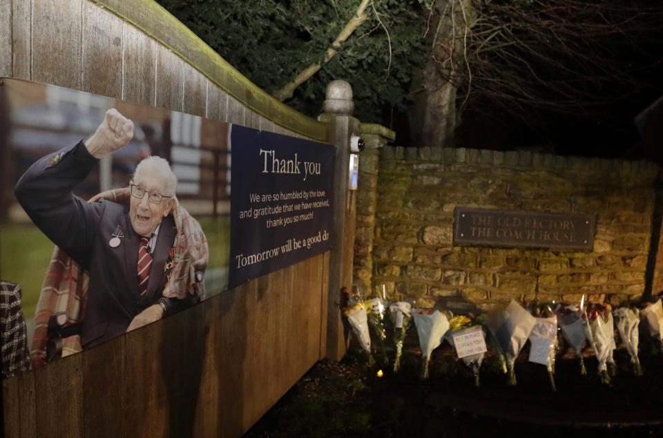 Flowers are placed near the home of Captain Tom Moore in Marston Moretaine, England, Tuesday, Feb. 2, 2021. Tom Moore, the 100-year-old World War II veteran who captivated the British public in the early days of the coronavirus pandemic with his fundraising efforts, has died, Tuesday Feb. 2, 2021. (AP Photo/Kirsty Wigglesworth)