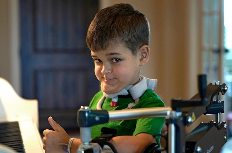 Braden Scott, who was diagnosed with AFM in 2016 and was almost completely paralyzed, gives a thumbs-up as he pauses while practicing on the piano in Tomball, Texas, in March 2019. (Photo: ASSOCIATED PRESS)