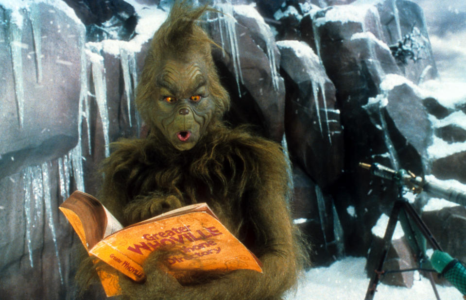 Jim Carrey looking through phone directory in a scene from the film 'How The Grinch Stole Christmas', 2000. (Photo by Universal/Getty Images)