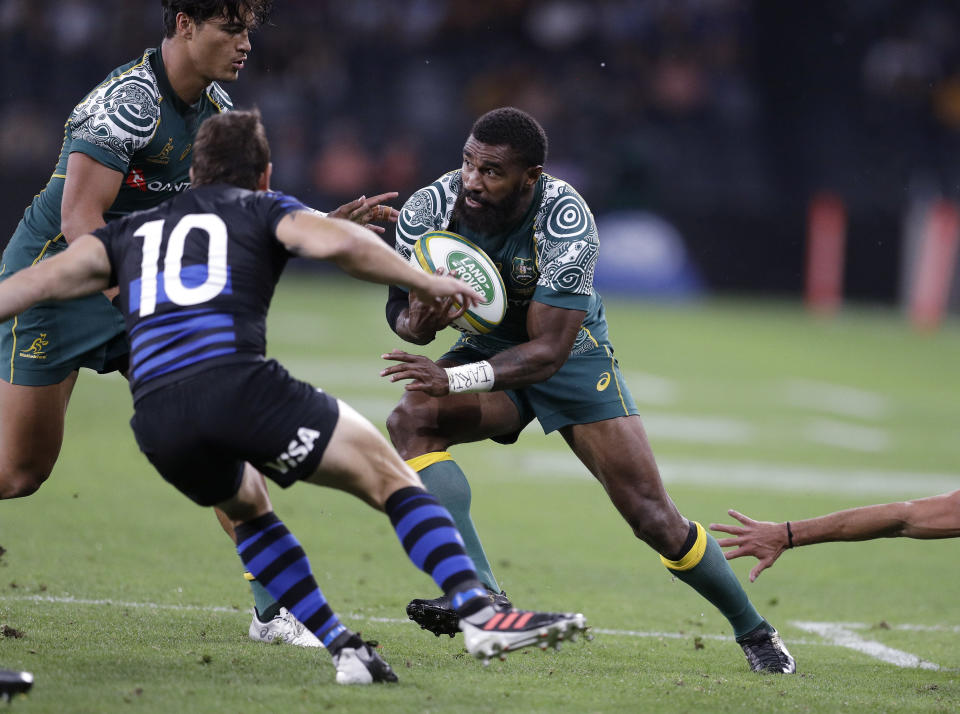Australia's Marika Koroibete, right, charges toward Argentina's Nicolas Sánchez during their Tri-Nations rugby union match in Sydney, Australia, Saturday, Dec. 5, 2020. (AP Photo/Rick Rycroft)