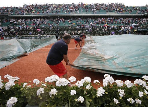 Employees pull on a protective canvas as rain delays the semifinal match opposing Russia's Maria Sharapova to Belarus' Victoria Azarenka during the French Open tennis tournament at the Roland Garros stadium Thursday, June 6, 2013 in Paris. (AP Photo/Petr David Josek)
