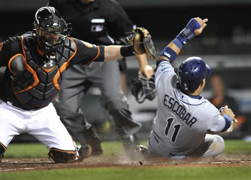 Tampa Bay Rays Yunel Escobar, right, is safe at the plate on a single by Desmond Jennings as Baltimore Orioles catcher Matt Wieters tries to make the tag in the fifth inning of a baseball game Friday, May 17, 2013, in Baltimore. (AP Photo/Gail Burton)