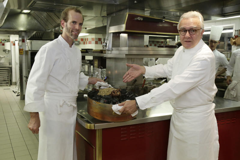 This Oct. 9, 2012 photo shows American Chef Dan Barber, left, and Alain Ducasse displaying a Cossabow Pig plate in the kitchen of the Plaza Athenee in Paris. He fires up the succulent pork over gnarled, carbonated pig bones, grows sweet greens in a soil mixed with pumice that's left over by the hazelnut oil industry and he's creating a new kind of wheat, named after himself _ Dan Barber. (AP Photo/Michel Euler)