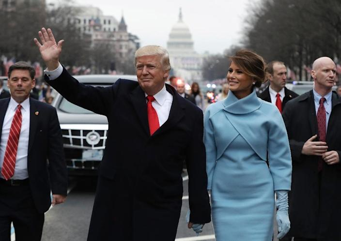 President Donald Trump waves as he walks with first lady Melania Trump during the inauguration parade on Pennsylvania Avenue on January 20, 2107 (AFP Photo/Evan Vucci)