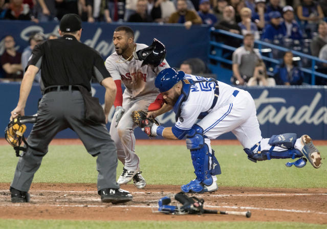 Toronto Blue Jays catcher Russell Martin puts the tag on Boston Red Sox's Eduardo Nunez for the out as home plate umpire Scott Barry watches during the ninth inning of a baseball game Tuesday, April 24, 2018, in Toronto. (Fred Thornhill/The Canadian Press via AP)