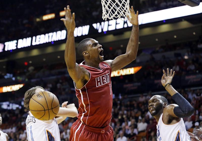 Miami Heat's Chris Bosh, center, is fouled by Charlotte Bobcats' Al Jefferson, right, during the first half of an NBA basketball game Sunday, Dec. 1, 2013, in Miami. (AP Photo/Lynne Sladky)