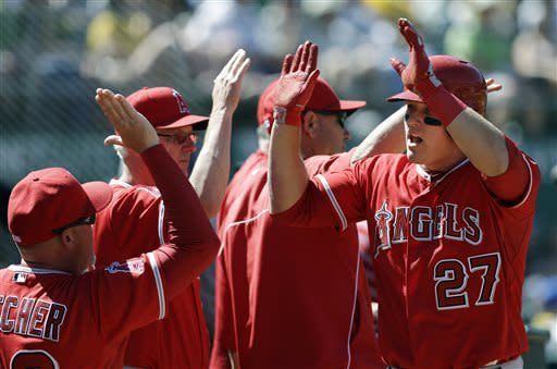 Los Angeles Angels' Mike Trout (27) celebrates after scoring on a sacrifice by Albert Pujols during the eighth inning of a baseball game against the Oakland Athletics in Oakland, Calif., Wednesday, May 1, 2013. (AP Photo/Jeff Chiu)