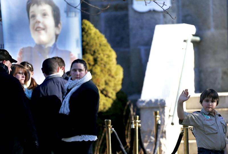 A boy wearing a Boy Scouts of America uniform waves at media while standing next to portrait of Benjamin Andrew Wheeler, outside of Trinity Episcopal Church before funeral services for Wheeler, Thursday, Dec. 20, 2012, in Newtown, Conn. Wheeler, 6, died when the gunman, Adam Lanza, walked into Sandy Hook Elementary School in Newtown, Dec. 14, and opened fire, killing 26 people, including 20 children, before killing himself. (AP Photo/Julio Cortez)