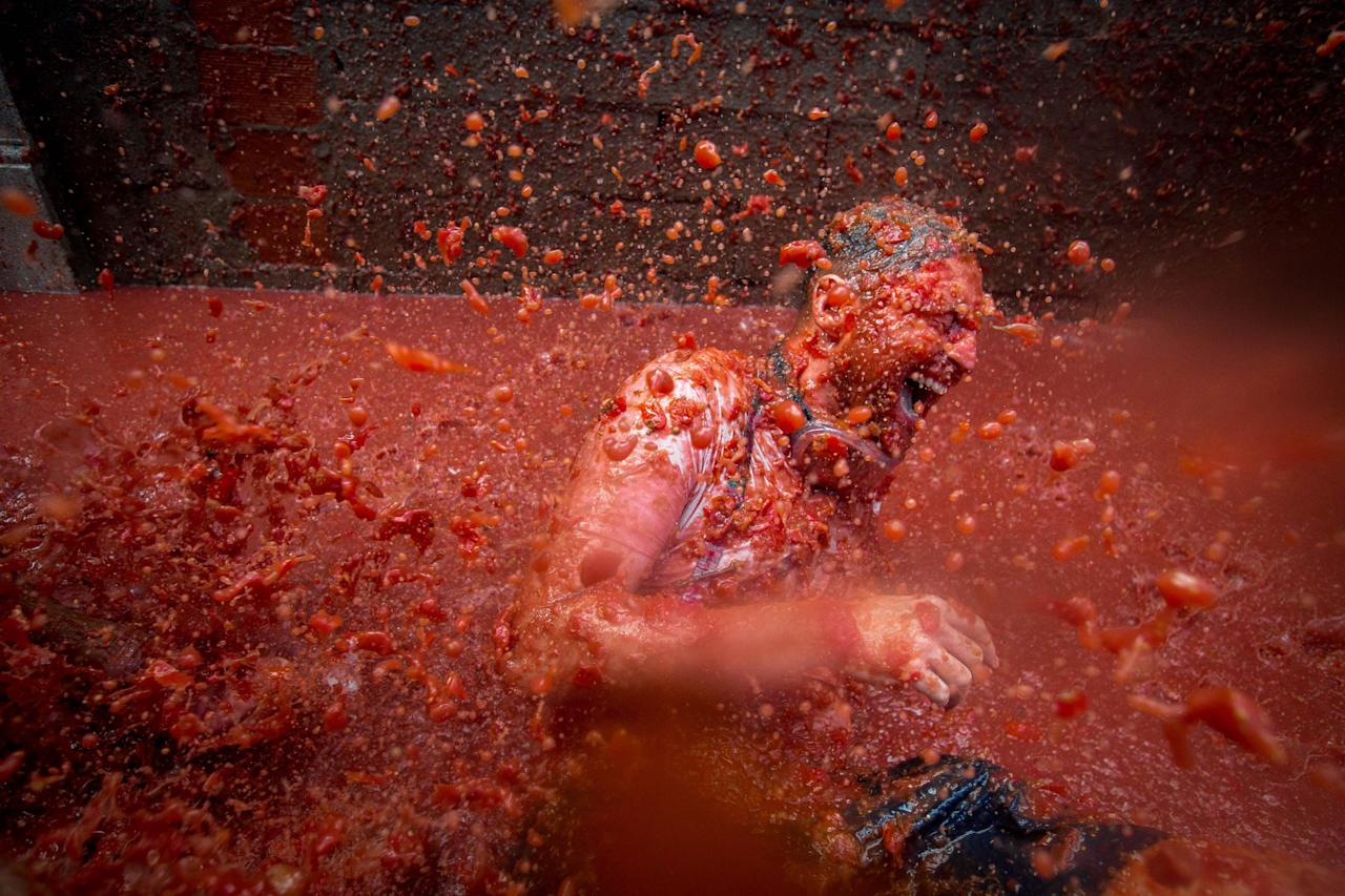 "A reveller is pelted with tomato pulp during the annual ""tomatina"" festivities in the village of Bunol, near Valencia on August 31, 2016."