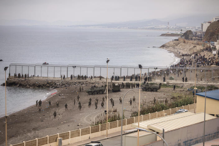 Spanish Army take positions next to the border of Morocco and Spain, at the Spanish enclave of Ceuta, on Tuesday, May 18, 2021. Ceuta, a Spanish city of 85,000 in northern Africa, faces a humanitarian crisis after thousands of Moroccans took advantage of relaxed border control in their country to swim or paddle in inflatable boats into European soil. Around 6,000 people had crossed by Tuesday morning since the first arrivals began in the early hours of Monday, including 1,500 who are presumed to be teenagers. (AP Photo/Javier Fergo)