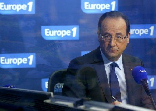 Francois Hollande is seen through the glass of an Europe 1 radio station studio on December 21, 2012 in Paris