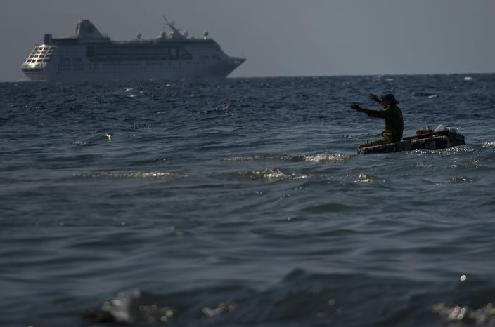A man fishes in the sea on a makeshift raft while the Empress of the Seas, a Royal Caribbean vessel, leaves the harbor in Havana, Cuba, Wednesday, June 5, 2019. Major cruise lines on Wednesday immediately began dropping stops in Cuba from their itineraries and hastily rerouting ships to other destinations including Mexico, after the Trump administration's new restrictions on travel to Cuba. (AP Photo/Ramon Espinosa)