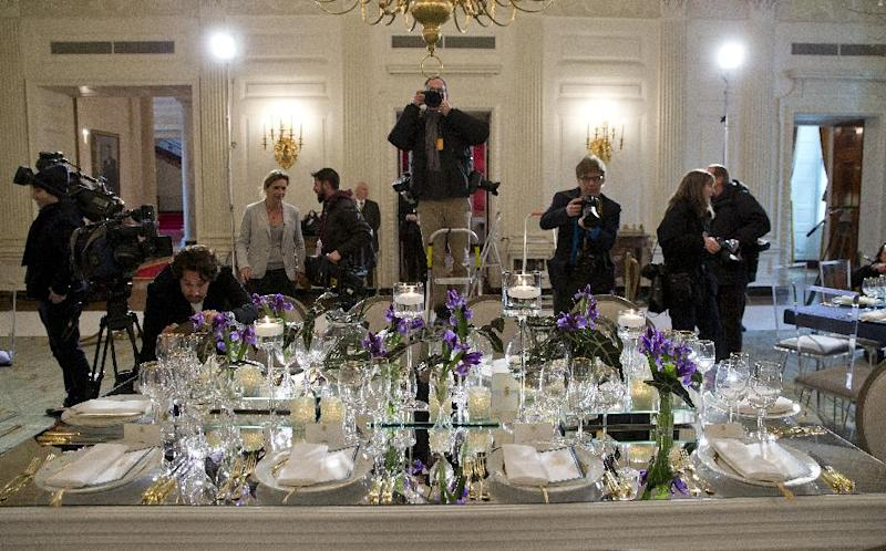 Members of the media gather around a table setting during a press preview in the State Dining Room of the White House in Washington, Monday, Feb. 10, 2014, ahead of Tuesday's State Dinner for French President François Hollande. First lady Michelle Obama's office gave the media, and by extension, the public, a peek at the elegant place settings, colorful flower arrangements and other details of the soiree. At least part of the evening's event will take place in a huge white tent going up on the South Lawn. (AP Photo/ Evan Vucci)