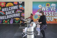 Women wearing face masks push strollers past signage in Melbourne, Australia, Wednesday, Oct. 28, 2020. Australia's second largest city of Melbourne which was a coronavirus hotspot emerges from a nearly four-months lockdown, with restaurants, cafes and bars opening and outdoor contact sports resuming on Wednesday. (AP Photo/Asanka Brendon Ratnayake)