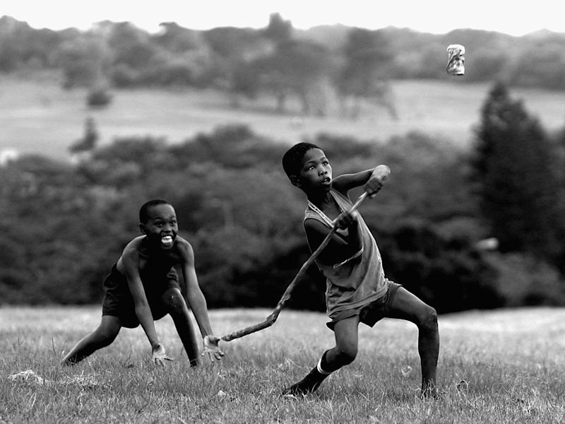 South African children playing cricket with a stick and a Coke can: Getty